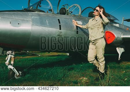 Full length portrait of a beautiful woman pilot wearing uniform and sunglasses posing at her fighter jet. Military and civil aircraft.