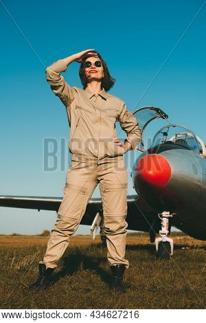 Confident smiling female pilot poses in front of the plane looking into the sky. Commercial and military aviation. Full length portrait on the airfield in the background of a blue sky.