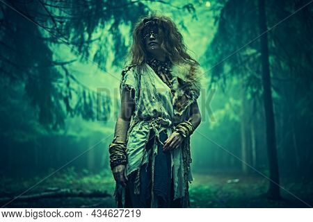 Portrait of a frightening forest witch with a mask covering her eyes standing in a gloomy mysterious forest. Woman shaman. Paganism. Death ritual. Halloween.
