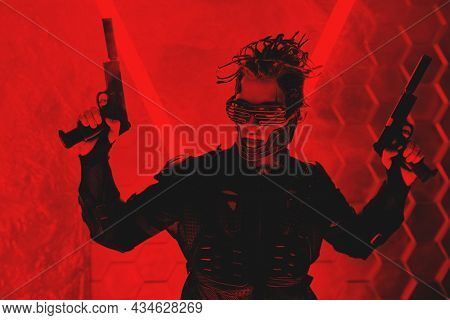 Warrior of the future. A brave cyberpunk warrior in protective uniform standing on alert with weapons in his hands in red light. Game, virtual reality.
