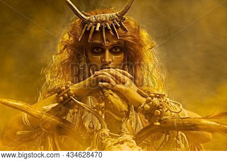 Portrait of a shaman woman in ritual clothes and with a staff in her hand, surrounded by a mystical haze. Ethnic traditions. Paganism. Halloween.
