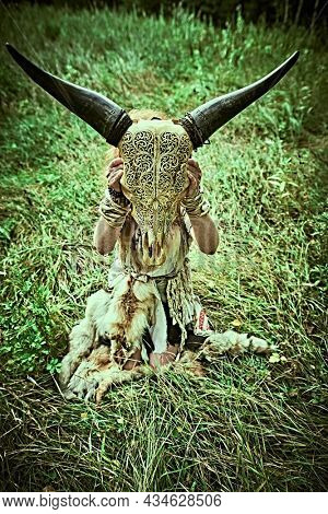 Female shaman in ethnic dress sits in a clearing in the forest and holds the skull of an animal in front of her. Mystical ritual. Fantasy concept, magic. Paganism. Halloween.