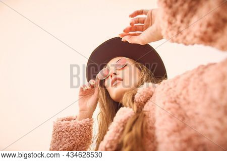 Bright young girl with stylish hat and glasses dressed in a fashionable pink fur coat poses in the background of a grey autumn sky. Autumn fashion.