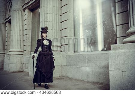 An elegant 19th century lady strolls down a city street. History and Fashion of the late 19th - early 20th century. Full length portrait.