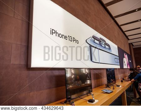 Paris, France - Sep 24, 2021: Customers Under Large Poster Of Iphone 13 Pro At The Apple Store As La