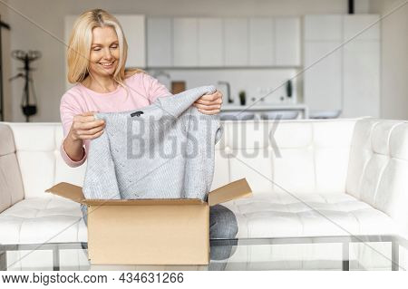 Satisfied Stylish Mid Age Blonde Woman Opens Parcel Carton Box, Unpacking Received Gift, Feeling Cur