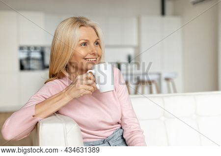 A Calm And Peaceful Middle-aged Woman Takes A Break, Rests With A Cup Of Hot Tea On The Couch At Hom