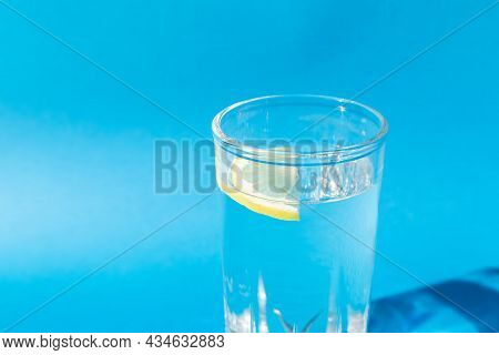 Fresh Clean Water In A Glass With A Slice Of Lemon On A Blue Background In Bright Sunlight. Live Wat