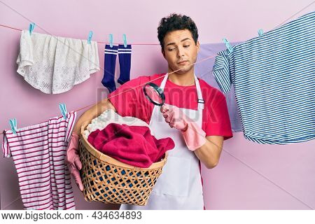 Handsome hispanic man doing laundry holding wicker basket looking for a stain in shock face, looking skeptical and sarcastic, surprised with open mouth