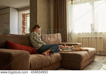 Portrait Of Young Tired And Depressed Mother Sitting On Couch, Unemotionally Looking At Her Infant B