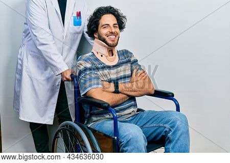 Handsome hispanic man sitting on wheelchair wearing neck collar happy face smiling with crossed arms looking at the camera. positive person.