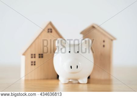 Wooden House With White Piggy Bank On Wooden Table. Saving Money For Buying House, Financial Plan Ho