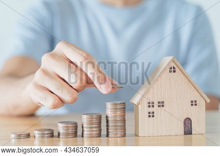 Man Hand Put Coin On Coins Stack With Wooden House On Wood Table. Saving Money For Buying House, Fin