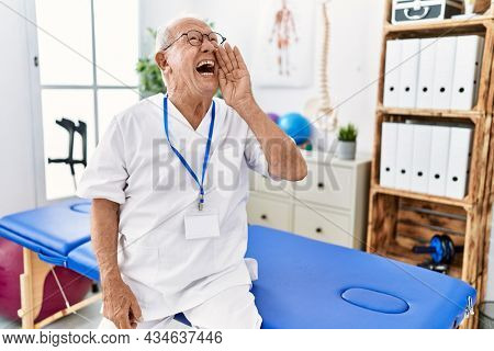 Senior physiotherapy man working at pain recovery clinic shouting and screaming loud to side with hand on mouth. communication concept.
