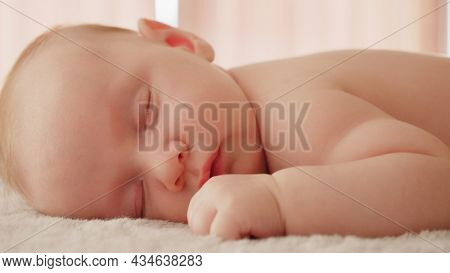 Healthy infant sleeping at home. Beautiful small baby sleeping. Close-up of infant sleeping. Macro shot of a small caucasian baby resting. Shot of napping child, afternoon nap.