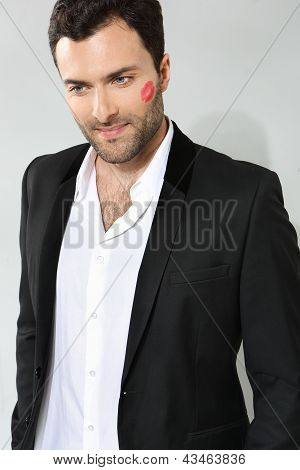 Young caucasian businessman with lipstick kiss mark on his cheek