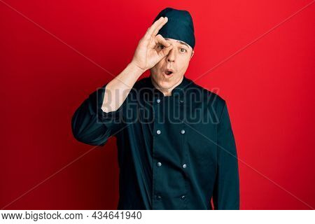 Handsome young man wearing professional cook uniform and hat doing ok gesture shocked with surprised face, eye looking through fingers. unbelieving expression.
