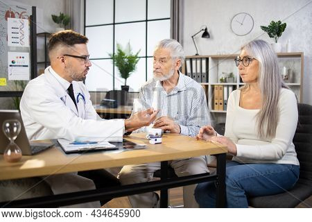 Caucasian Male Physician In White Lab Coat And Eyewear Prescribing Medicines To Mature Couple, Sitti