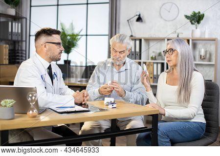 Caucasian Medical Worker White Lab Coat And Eyewear Prescribing Treatment To Mature Couple That Sitt