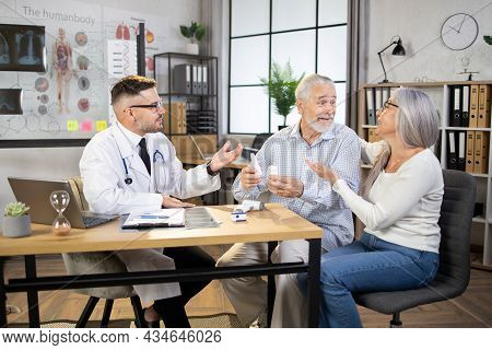 Caucasian Male Doctor In White Lab Coat And Eyeglasses Talking With Happy Senior Couple At His Priva