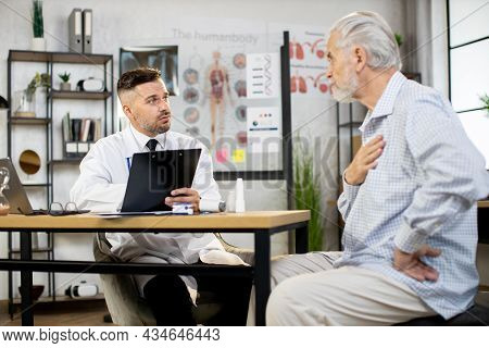 Competent Male Doctor Writing On Clipboard While Listening To Senior Patient At Private Office. Worr