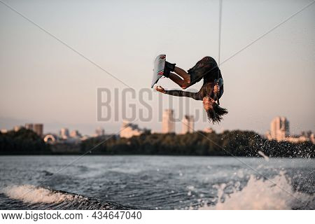 Active Strong Man Rider Holds Rope And Making Extreme Jump Showing Trick On Wakeboard.