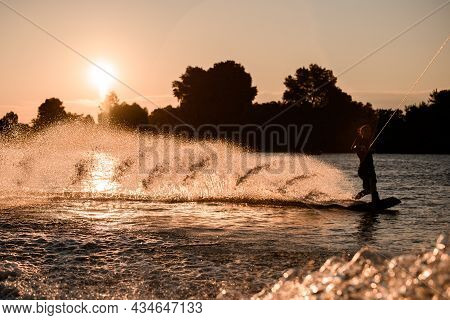 Beautiful View Of Active Male Rider Holds Rope And Riding On Wakeboard On Water Surface At Sunset.