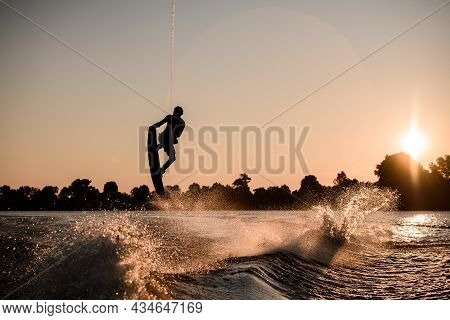 Beautiful View Of Dark Silhouette Of Active Male Rider Holds Rope And Making Extreme Jump On Wakeboa