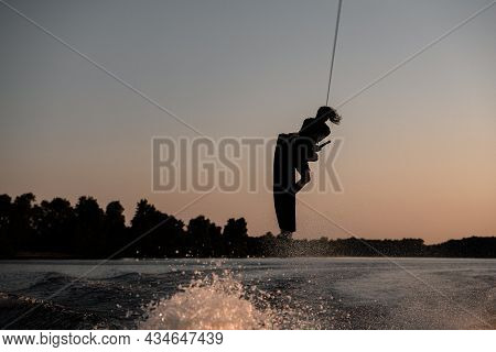 Silhouette Of Active Male Rider Holds Rope And Making Extreme Jump On Wakeboard At Sunset.