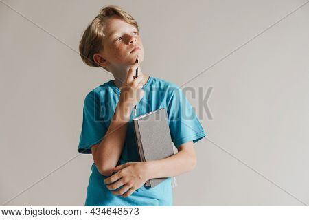 Portrait of a pensive casual preteen boy in t-shirt standing over isolated gray wall background holding book
