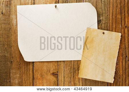 Mottled Beige Paper Nailed To Distressed Wooden Wall