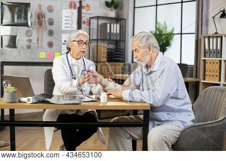 Qualified Female Mature Doctor In Coat Bandaging Injured Forearm Of Senior Gray-haired Male Patient.