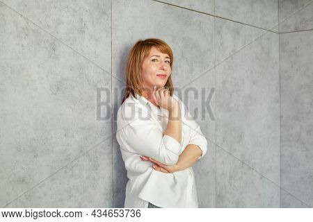 Happy Mature Mid Adult Business Woman In White Shirt On Grey Banner Background