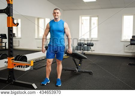 A Cute Young Coach Inspires Confidence, A Sports Body, Poses On The Simulator In The Gym. Muscular B