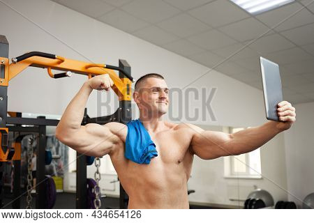 A Muscular Handsome Man Coach Is Photographed After Training, Resting. Phone, Tablet, Video Call, Mo