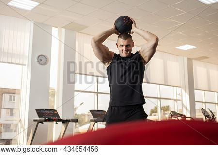 A Muscular Coach Throws The Ball On A Trampoline, A Muscle Trainer, A Gym. Portrait Of A Beautiful M