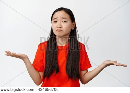 Puzzled Asian Girl Shrugging, Spread Hands Sideways And Staring Confused, Dont Know, Cant Help You,
