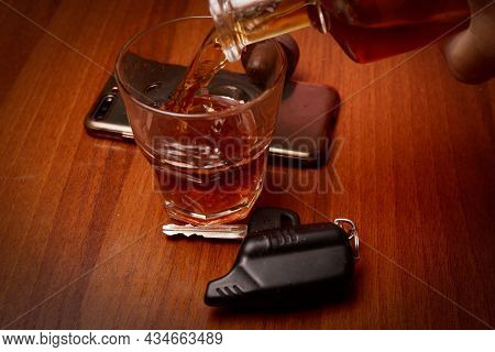 A Man Pours Alcohol Into A Glass, Next To Car Keys.drunkenness At The Wheel