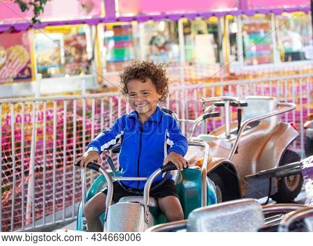 Cute mixed race little boy enjoying a ride on a fun carnival carousel ride. A happy boy Smiling and having fun riding a amusement ride at the summer carnival