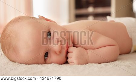 A small healthy baby being active in the morning. Cute infant being energetic on a sunny day. Baby stare. Beautiful caucasian baby at home stareing into camera.