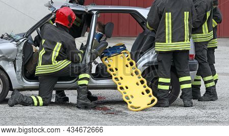 Firefighters In Action During The Rescue Of The Injured After The Car Accident With The Stretcher To