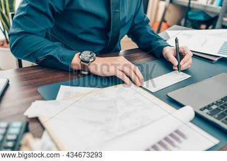 Business Man Hand Writing And Signing White Blank Bank Check Book And Dollar Bill, Coin, Laptop And