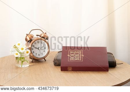 Bible And Notebook On The Table With An Alarm Clock By The Window. Time For Learning Bible Concept