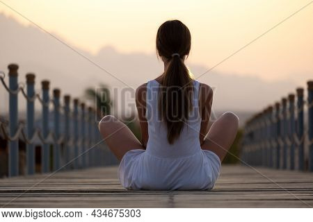 Young Woman In Light Dress Relaxing On Warm Sunny Morning On Sea Shore. Summer Vacation And Travelli