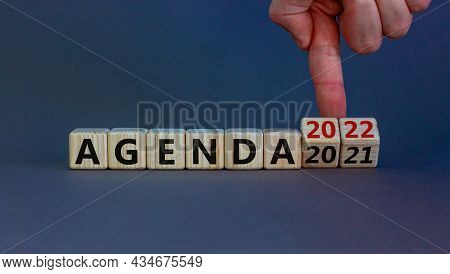 Planning 2022 Agenda New Year Symbol. Businessman Turns Wooden Cubes And Changes Words 'agenda 2021'