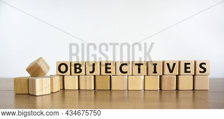 Objectives Symbol. The Word Objectives On Wooden Cubes. Beautiful Wooden Table, White Background. Bu