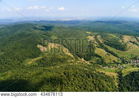 Aerial View Of Mountain Hills Covered With Dense Green Lush Woods On Bright Summer Day.