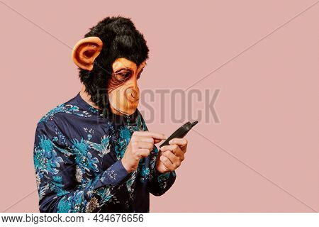 a young man wearing a monkey mask dialing a number in an old mobile phone, against a pink background