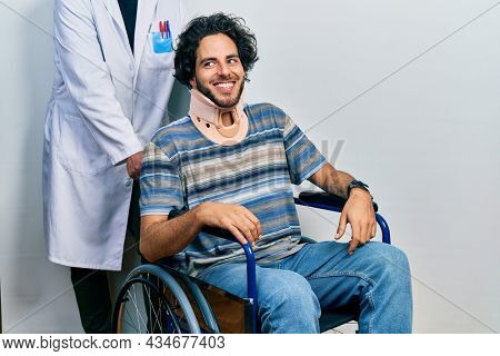 Handsome hispanic man sitting on wheelchair wearing neck collar looking away to side with smile on face, natural expression. laughing confident.