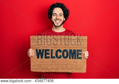 Handsome hispanic man holding welcome doormat smiling with a happy and cool smile on face. showing teeth.